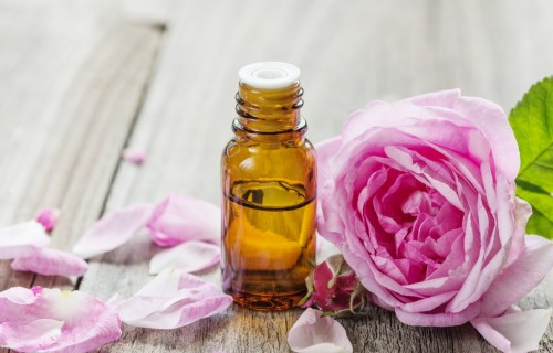 Dark glass vial with rose essential oil and flower of pink rose on a wooden background, with space for text