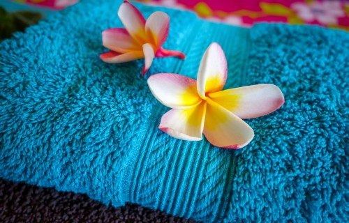White tiare flowers on a blue towel. Zen spa background