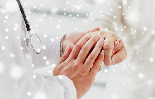 medicine, age, support, healthcare and people concept - close up of doctor or nurse holding senior man hand at hospital over snow